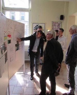 Abbildung 1 Haus5-Geschäftsführer Dieter Sanlier erklärt Gästen (Hr. Dr. Färber vom Panoptikum St. Pauli, Hr. Patett) an der Schautafel einzelne Schritte im